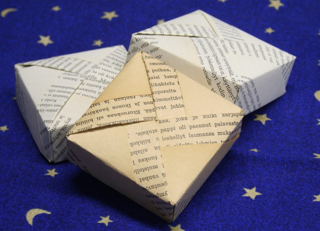 """Joululahjojen ekologinen paketointi: Kolme origami-taiteltua rasiaa. Etummaisessa rasiassa lukee """"pappi oli paennut palavasta"""", sillä taittelupaperin teksti oli jäänyt tarkistamatta."""