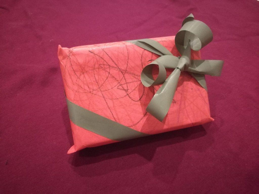 Joululahjojen ekologinen paketointi: Pieni punainen paketti, johon pieni lapsi on piirtänyt tummia koukeroita.  Paketissa on vihreä nauha ja rusetti.