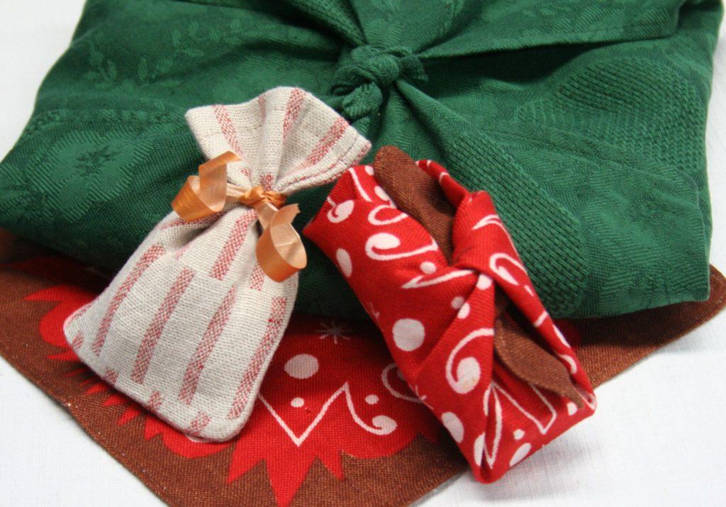 Joululahjojen ekologinen paketointi: Kolme kankaista pakettia. Kaksi paketeista on solmittu japanilaiseen furoshiki-tyyliin kierrätyskeskuksesta saatuihin, jouluisiin liinoihin. Yksi paketeista on kuparinhohtoisella nauhalla solmittu, pellavainen pussi.