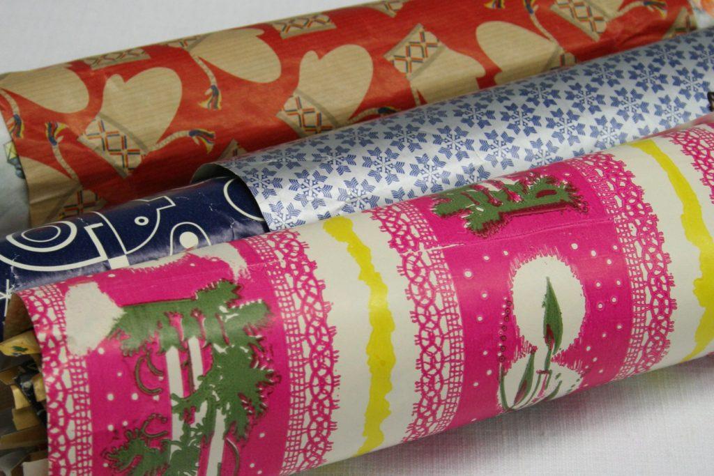 Joululahjojen ekologinen paketointi: Vanhoja joululahjapapereita käärittyinä rullille. Etummaisena paperi, jossa on vahvaa pinkkiä ja kynttilöitä. Paperi on mahdollisesti 1970-luvulta. Keskimmäisen käärön päällimmäiset paperit edustavat mahdollisesti 1990-lukua.