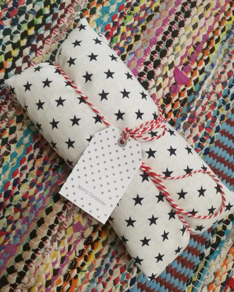 """Joululahjojen ekologinen paketointi: Kauniilla räsymatolla kuvattu valkoinen, tähtikuosinen kauratyyny on kietaistu punavalkoiseen nauhaan ja viimeistelty tyyliin sopivalla pakettikortilla, jossa lukee """"Merry Christmas""""."""