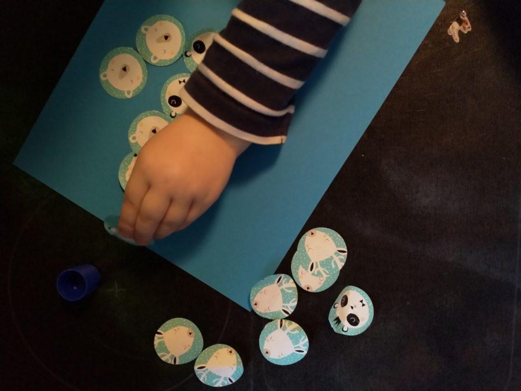 Joululahjojen ekologinen paketointi: Pieni käsi liimaa vaaleansiniselle paperille vaaleansinisestä lahjapaperista leikattuja, ympyrän muotoisia eläinten kuvia.
