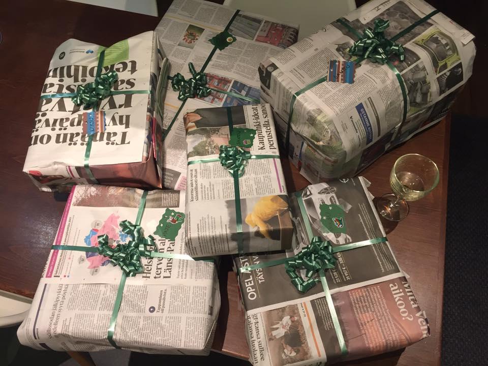 Joululahjojen ekologinen paketointi: Ahkeran paketoijan työn tulos: Kasa sanomalehtipaperiin paketoituja lahjoja.