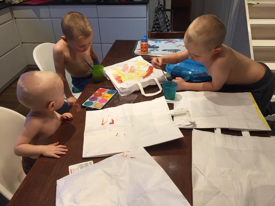 Joululahjojen ekologinen paketointi: Pienet lapset maalaavat kuvia paperisiin kasseihin keittiönpöydän ääressä.