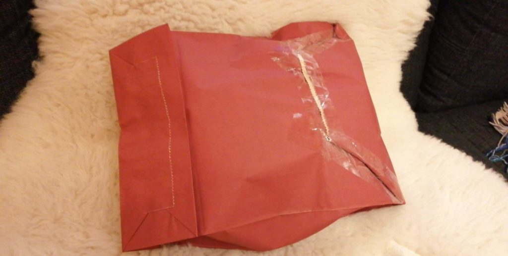 Joululahjojen ekologinen paketointi: Lahjapussi on kierrätetty postipaketiksi. Kuva pussin takapuolelta, jonne on riittänyt hyvä taittovara pussin sulkemista varten.